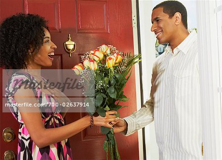 Woman Receiving Flowers from Man in Doorway Stock Photo - Rights-Managed, Image code: 700-02637914