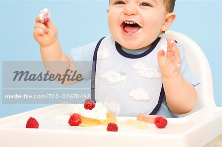 Baby Eating in High Chair Stock Photo - Rights-Managed, Image code: 700-02670492