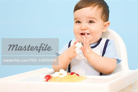 Baby Eating in High Chair Stock Photo - Rights-Managed, Image code: 700-02670493