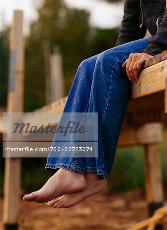 Girl Sitting on the Edge of a Wooden Dock at Sunset Stock Photo - Rights-Managed, Image code: 700-02723074