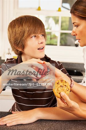 Mother Trying to Get Son to Eat an Apple Instead of a Cookie Stock Photo - Rights-Managed, Image code: 700-02738798