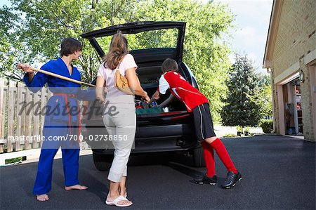 Boys in Karate and Soccer Uniforms Helping Mom Pack the Car Stock Photo - Rights-Managed, Image code: 700-02738850