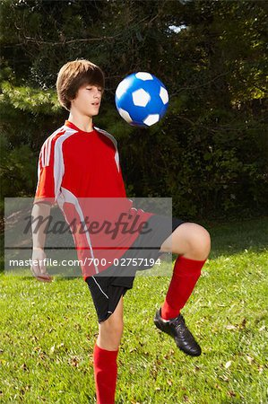 Teenage Boy Bouncing Soccer Ball on Knee Stock Photo - Rights-Managed, Image code: 700-02757194
