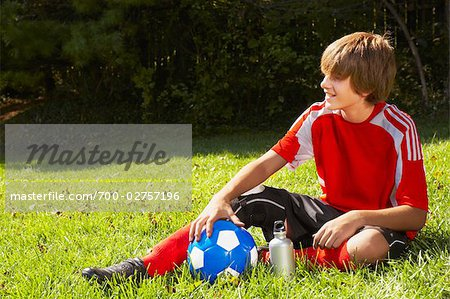 Teenage Boy in Soccer Uniform Sitting on Grass with Soccer Ball Stock Photo - Rights-Managed, Image code: 700-02757196