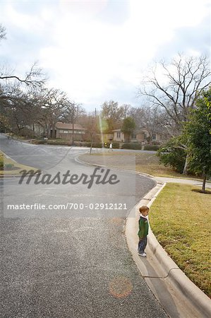 Boy Standing near Curb of Neighborhood Street, Austin, Texas, USA