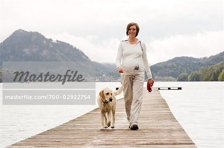 Pregnant Woman Walking on Dock With Her Dog Stock Photo - Rights-Managed, Image code: 700-02922754