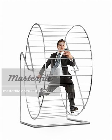 Businessman With an Electronic Organizer Running on a Hamster Wheel Stock Photo - Rights-Managed, Image code: 700-02922879