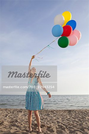 Woman on the Beach Holding a Bunch of Colourful Balloons Stock Photo - Rights-Managed, Image code: 700-02943254