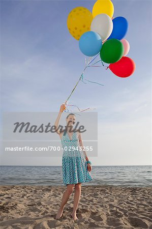 Woman on the Beach Holding a Bunch of Colourful Balloons Stock Photo - Rights-Managed, Image code: 700-02943255