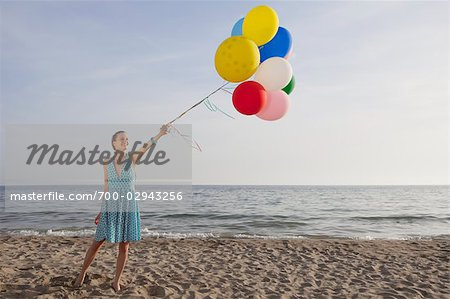 Woman on the Beach Holding a Bunch of Colourful Balloons Stock Photo - Rights-Managed, Image code: 700-02943256