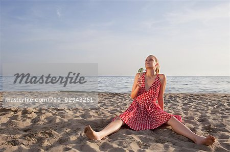 Woman With a Lollipop Sitting on the Beach Stock Photo - Rights-Managed, Image code: 700-02943261