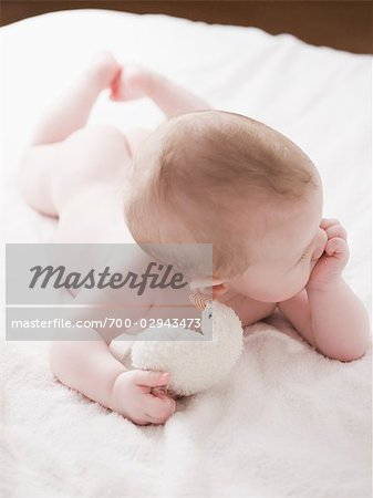 Baby Lying on Bed With Toy Stock Photo - Rights-Managed, Image code: 700-02943473