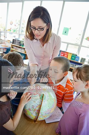 Children and Teacher in Grade One Classroom Looking at Globe Stock Photo - Rights-Managed, Image code: 700-02989981