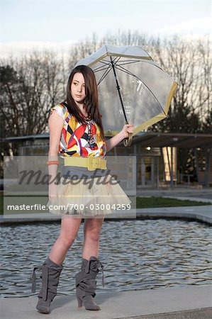 Young Woman Holding Umbrella by Water Fountain Stock Photo - Rights-Managed, Image code: 700-03004259