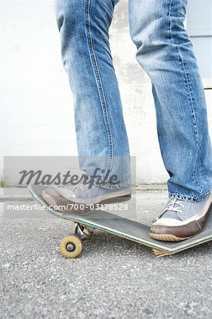 Teenager Standing on Broken Skateboard Stock Photo - Rights-Managed, Image code: 700-03178528