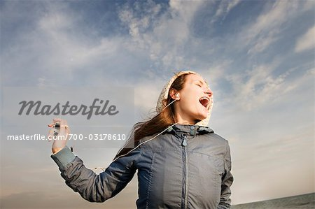 Woman Wearing Headphones Singing Along With Music Stock Photo - Rights-Managed, Image code: 700-03178610