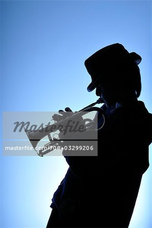 Silhouette of Boy Playing Trumpet