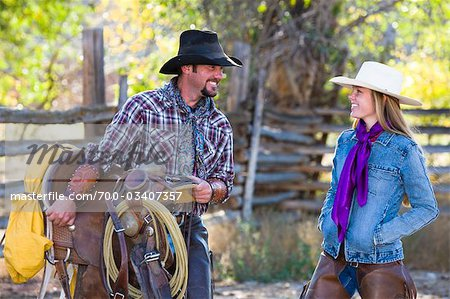 Cowboy Carrying Western Saddle and Talking with Cowgirl Stock Photo - Rights-Managed, Image code: 700-03407357