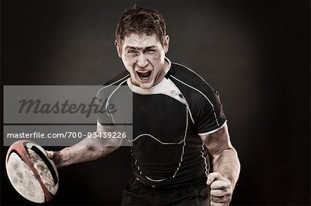 Dirty Rugby Player Holding Ball