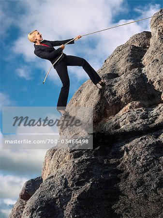 Businesswoman Climbing up Cliff