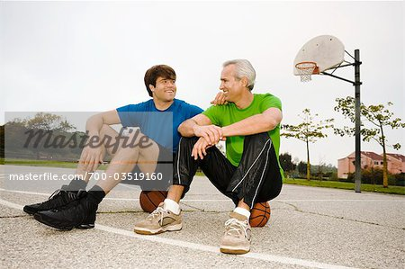 Father and Son Sitting on Basketballs on Court Stock Photo - Rights-Managed, Image code: 700-03519160