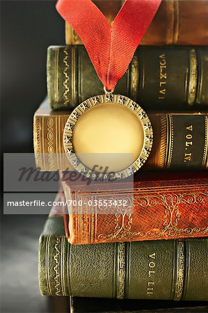 Close-up of Golden Medal with Leather Bound Books Stock Photo - Rights-Managed, Image code: 700-03553432