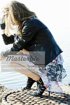 Woman Crouching on Manhole Stock Photo - Rights-Managed, Image code: 700-03615576