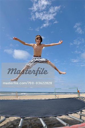 Boy on the Beach Jumping on Trampoline Stock Photo - Rights-Managed, Image code: 700-03622828