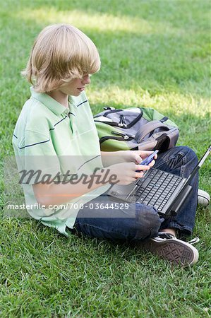 Boy with Laptop and Cell Phone Sitting on Grass Stock Photo - Rights-Managed, Image code: 700-03644529