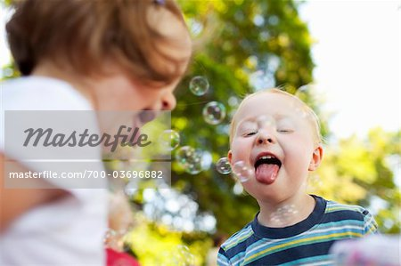 Boy and Girl Catching Bubbles with Tongues Stock Photo - Rights-Managed, Image code: 700-03696882