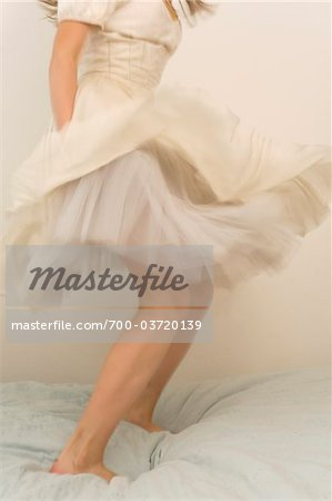 Girl Wearing Dress and Jumping on Bed Stock Photo - Rights-Managed, Image code: 700-03720139