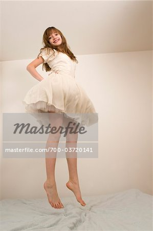 Teenage Girl Jumping on Bed Stock Photo - Rights-Managed, Image code: 700-03720141