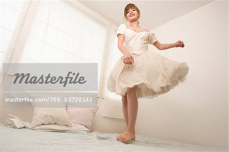 Teenage Girl Jumping on Bed Stock Photo - Rights-Managed, Image code: 700-03720142