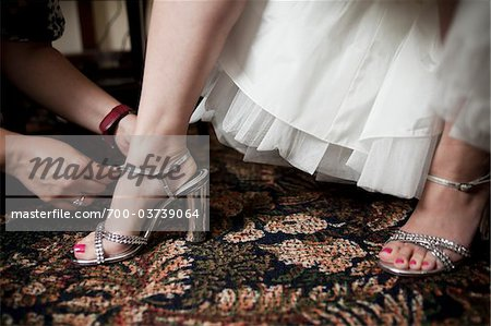 Helping Bride Buckle Shoes Stock Photo - Rights-Managed, Image code: 700-03739064