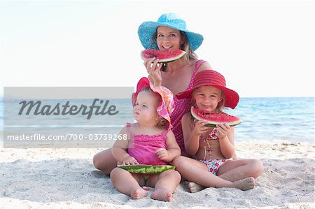 Mother with Daughers Eating Watermelon on Beach Stock Photo - Rights-Managed, Image code: 700-03739268