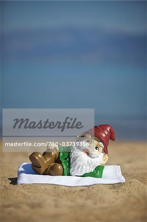 Garden Gnome Lying on Towel on Beach Stock Photo - Rights-Managed, Image code: 700-03739356