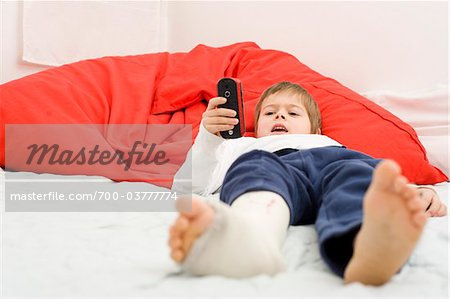 Boy with Cast on Leg Dialing Cell Phone Stock Photo - Rights-Managed, Image code: 700-03777774