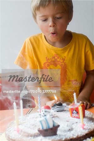Boy Blowing out Candles on Birthday Cake Stock Photo - Rights-Managed, Image code: 700-03777788
