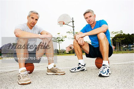 Two Men Sitting on Basketballs on Basketball Court Stock Photo - Rights-Managed, Image code: 700-03784261