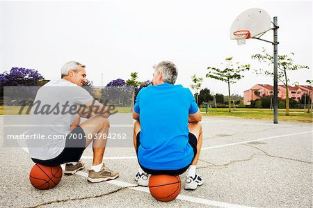 Two Men Sitting on Basketballs on Basketball Court Stock Photo - Rights-Managed, Image code: 700-03784262