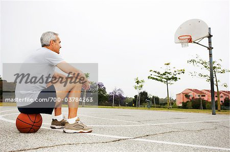 Man Sitting on Basketball on Basketball Court Stock Photo - Rights-Managed, Image code: 700-03784263