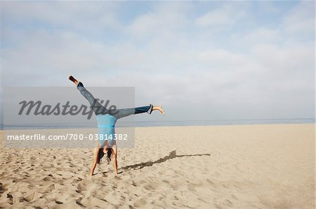 Woman Doing Cartwheel on Beach Stock Photo - Rights-Managed, Image code: 700-03814382
