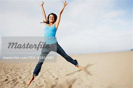 Woman Jumping on Beach Stock Photo - Rights-Managed, Image code: 700-03814383