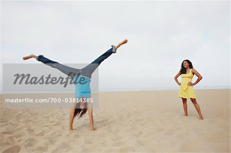 Young Woman Doing Cartwheel while Friend Watches Stock Photo - Rights-Managed, Image code: 700-03814385