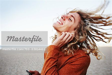 Young Man Listening Music on Beach Stock Photo - Rights-Managed, Image code: 700-03814401