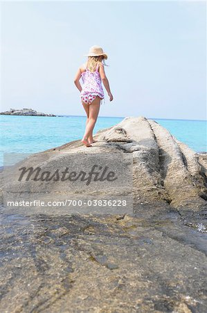 Girl Walking on Boulder at Beach Stock Photo - Rights-Managed, Image code: 700-03836228
