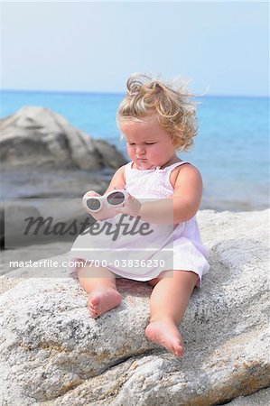 Little Girl with Sunglasses Sitting on Rock Stock Photo - Rights-Managed, Image code: 700-03836230