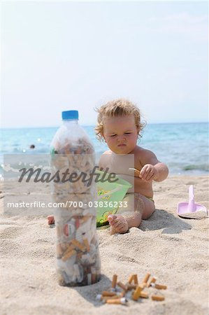 Girl Playing with Cigarette Butts on Beach Stock Photo - Rights-Managed, Image code: 700-03836233