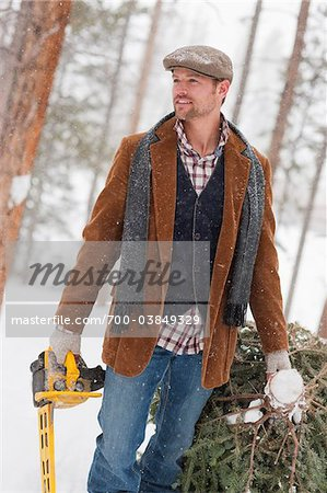 Man with Chainsaw Dragging Fresh Cut Tree Stock Photo - Rights-Managed, Image code: 700-03849329