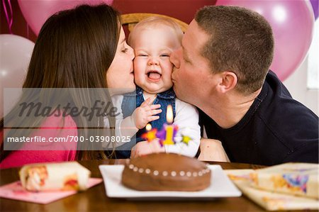 Parents Kissing Girl at First Birthday Party Stock Photo - Rights-Managed, Image code: 700-03908025